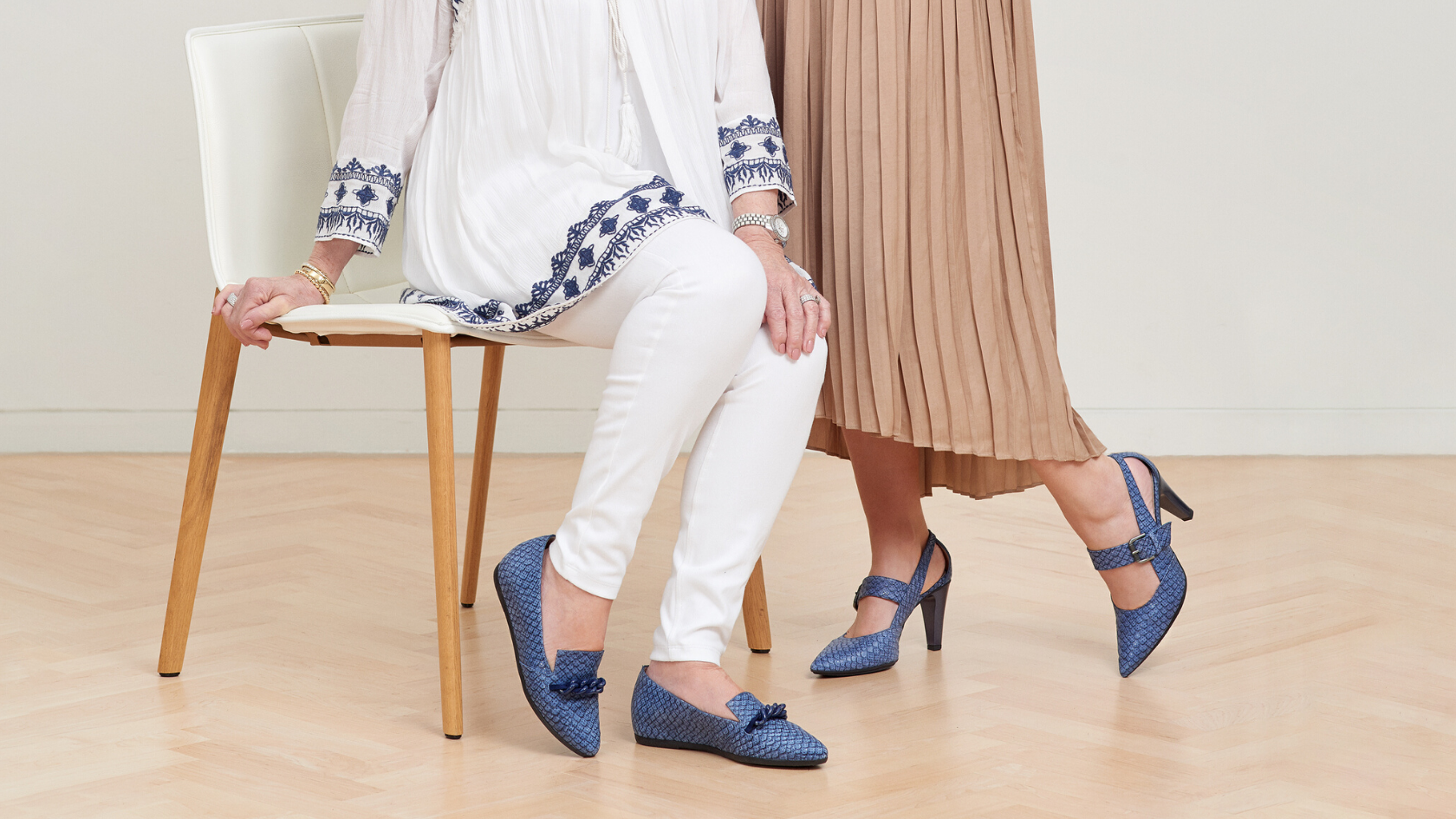 Image of two ladies wearing blue Hispanita shoes. One is sitting down wearing flats and the other is standing up wearing heels.