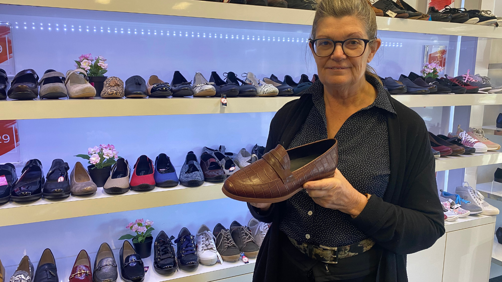 An older woman holding a brown leather loafer in front of a shoe display.