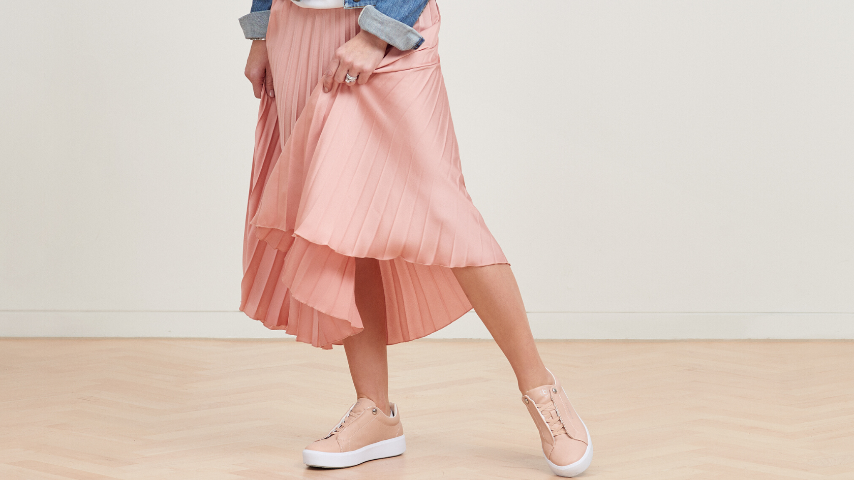 Lady posing in her pink rippled skirt with her pink bugatti sneakers in front of a neutral background