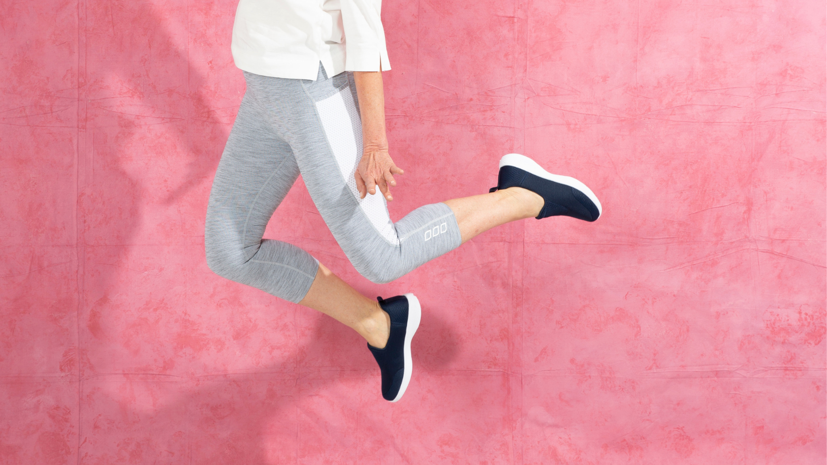 Snap shot of a woman jumping up in front of a pink background wearing slip on sneakers.